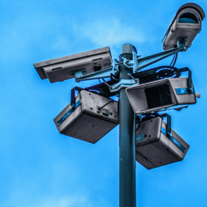 surveillance cameras pointing in every direction from the top of a pole, with the blue sky visible in the background.