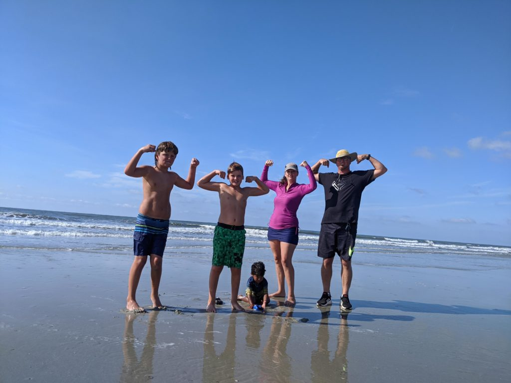 Beach picture with the ocean in the background.  Ben Jacqueline and 2 oldest boys are standing in their swimsuits and flexing muscled. The youngest son is sitting and playing in the sand.