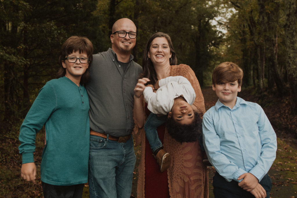 Family picture  outdoors with Ben, Jacqueline, and 3 boys. It is the fall and they are surrounded trees and leaves on the ground. It is a silly picture  with the 3 year old  bent over backwards goofing off.
