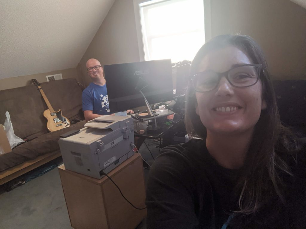Selfie of Jacqueline with brown hair and glasses, grinning at the camera. She's backlit heavily by a window, partially obscuring her face. Ben (bald with glasses, wearing a blue tshirt) is peeking around a monitor on a desk under the window. Behind him is a brown futon with an electric guitar sitting upright on it.