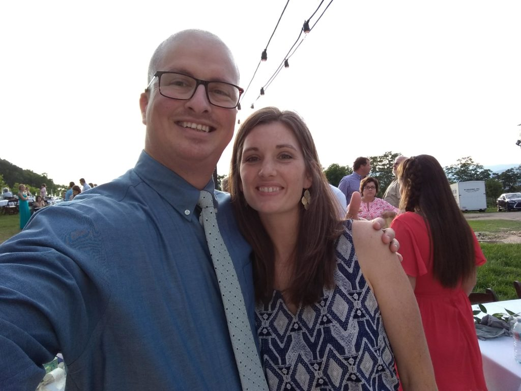 Selfie of Ben and Jacqueline at a n outdoor summer wedding reception. He is wearing a blue shirt and she is  wearing a sleeveless blue and grey dress.
