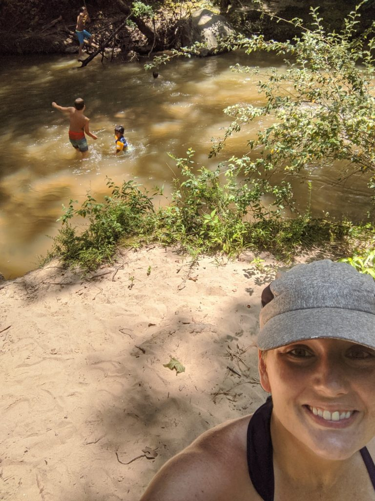Selfie of Jacqueline wearing a hat with the boys playing in a river behind her.