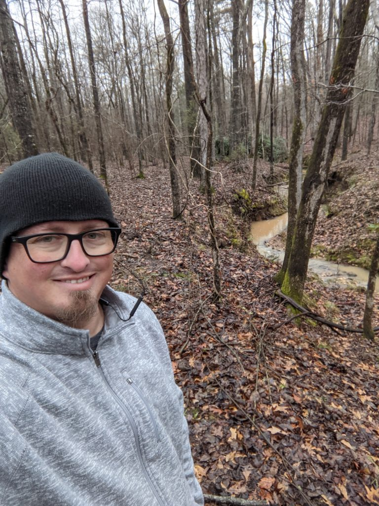 Selfie of Ben in the woods. He is wearing a black toboggan and grey jacket. There are leaves on the ground and a muddy creek behind him.